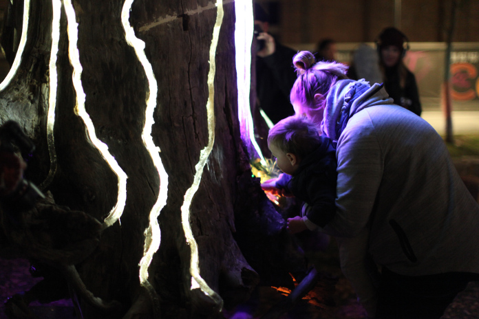 People interacting with the Adobe Heart Tree Light Sculpture