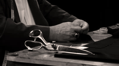 Close up of Tailor sewing a button onto a suit