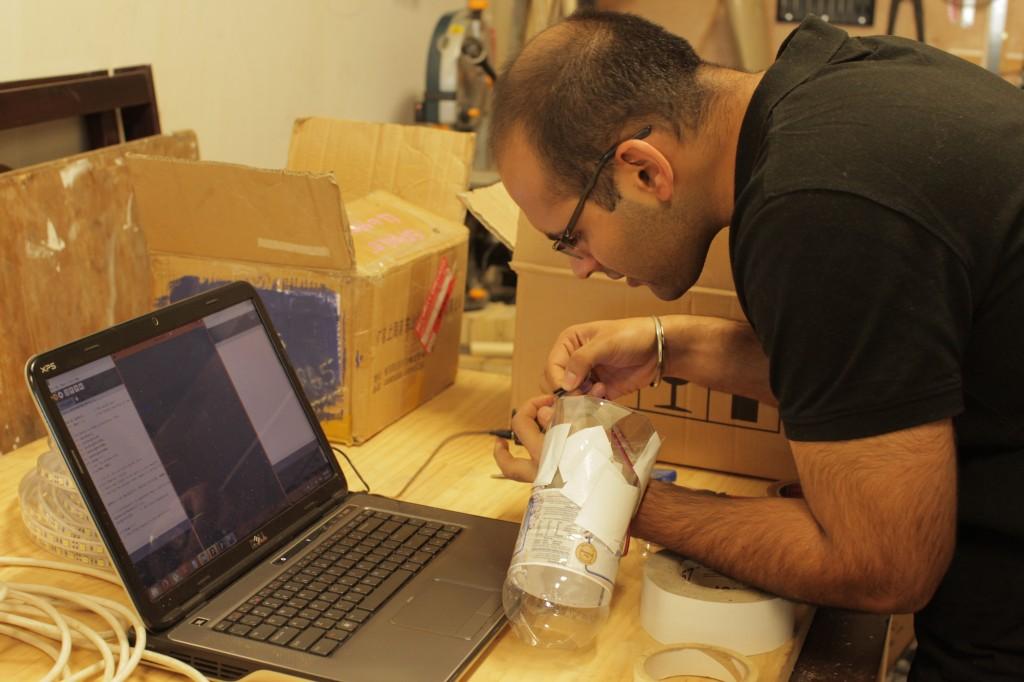 Man using soldering iron behind laptop