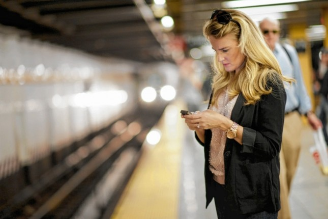 Woman texting on her phone at a train station