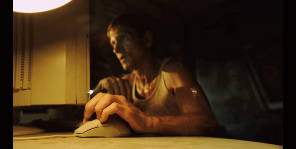 Man using computer in dark lighting