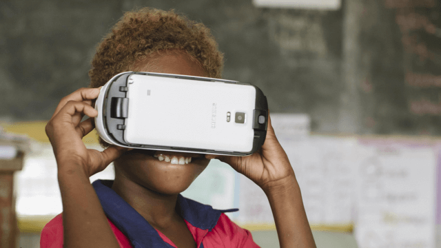 Child wearing Virtual Reality Goggles in Classroom.