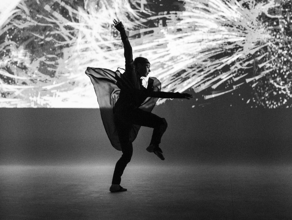 S1T2 Adobe Remix Dancer performing in front of lights