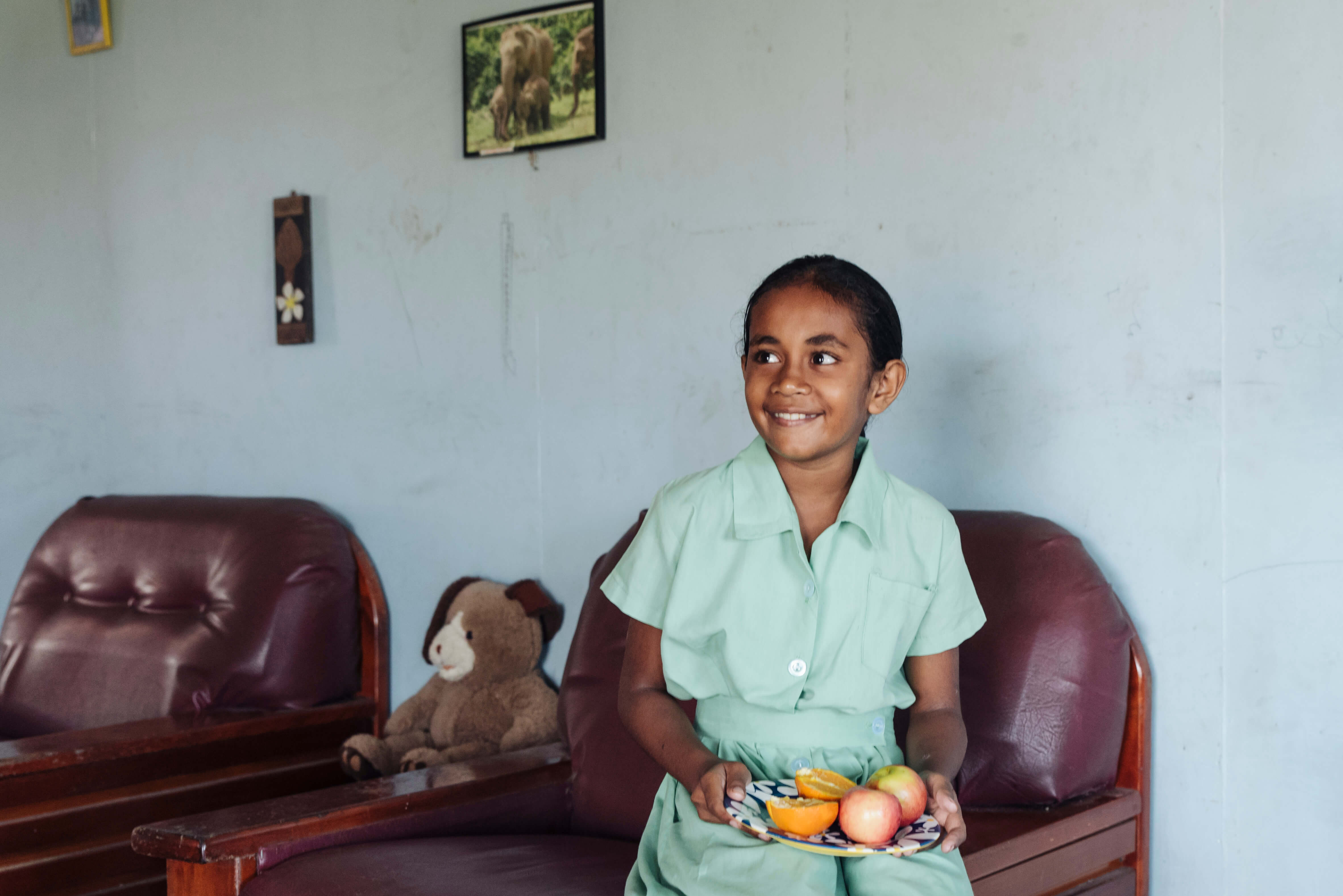Fijian student who participated in Beyond the Stars sits in her home holding a plate of fruits.
