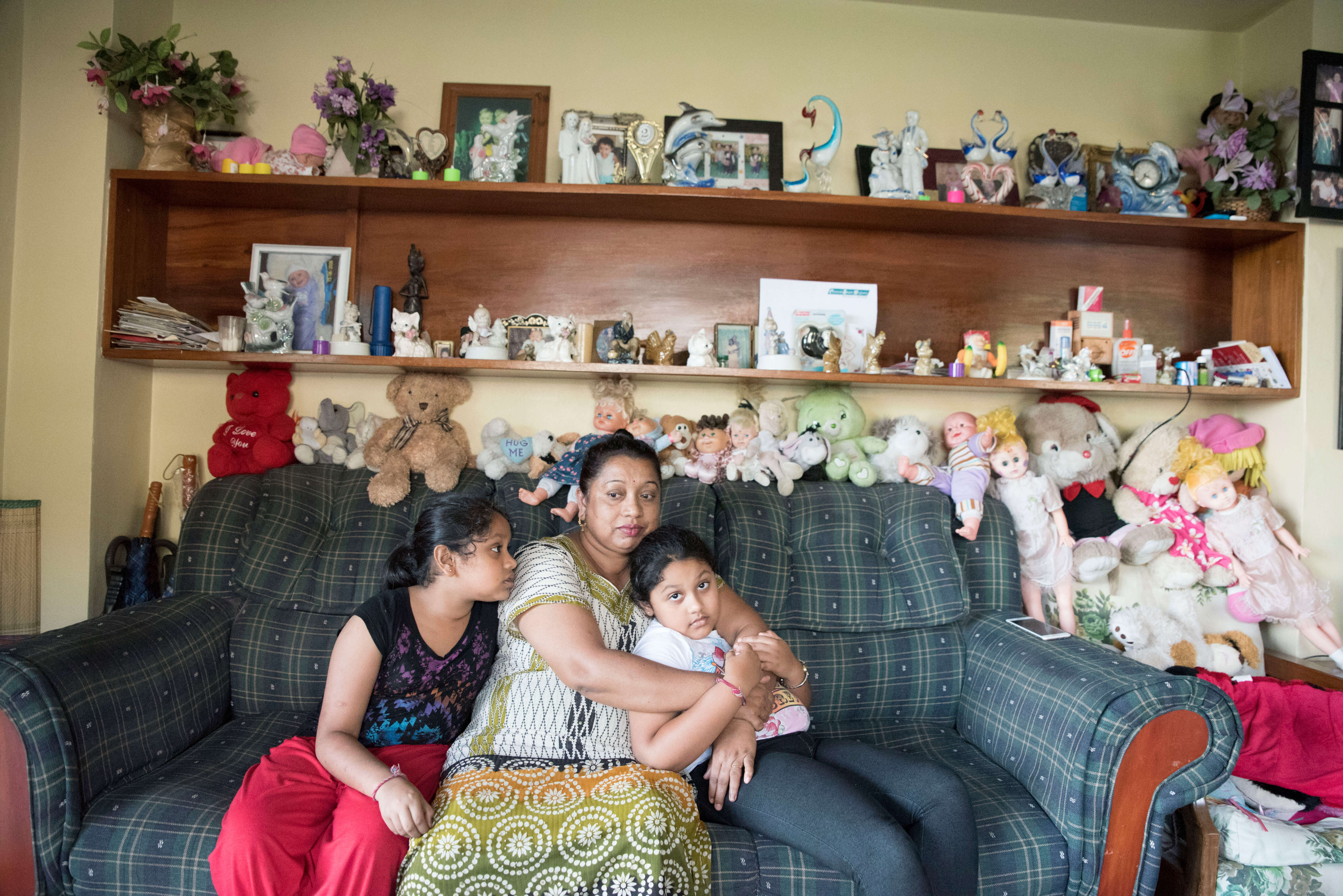 Family who used the Beyond the Stars educational pilot sits together in their home in Sigatoka, Fiji.