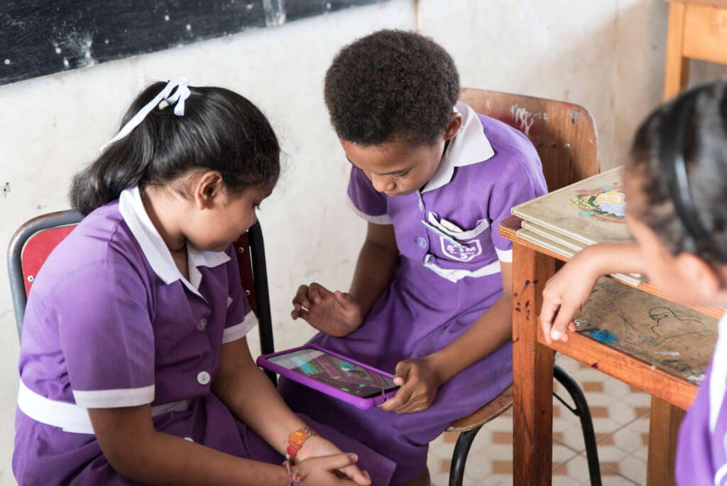 Three children in Fiji play the Beyond the Stars Mobile game in class