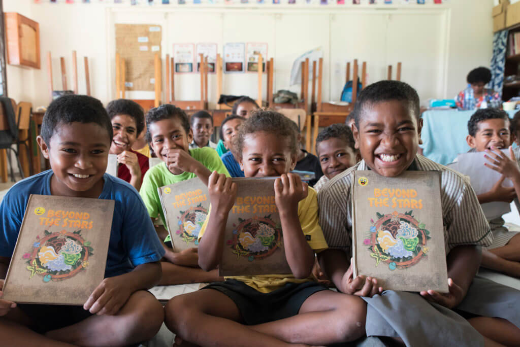 A class of smiling Fijian children hold up the Beyond the Stars storybook at school