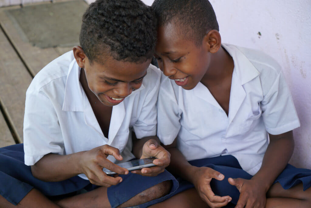 Two Fijian children play the Beyond the Stars Mobile game at school