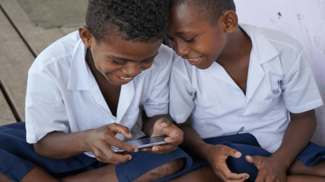 Two Fijian children play Beyond the Stars mobile game on a smartphone during school.
