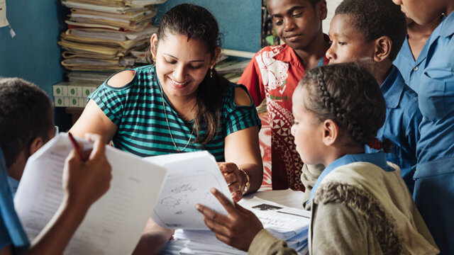 A teacher and group of students mark Beyond the Stars worksheets in a Fijian classroom.