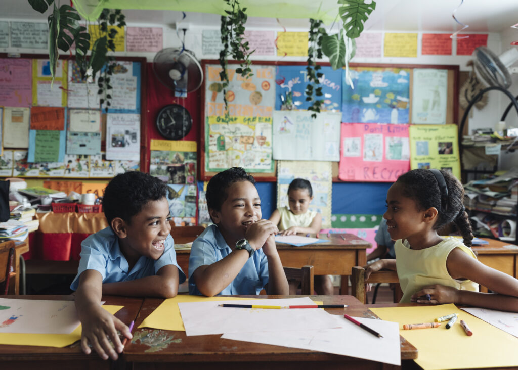 Three children play in a classroom in Fiji