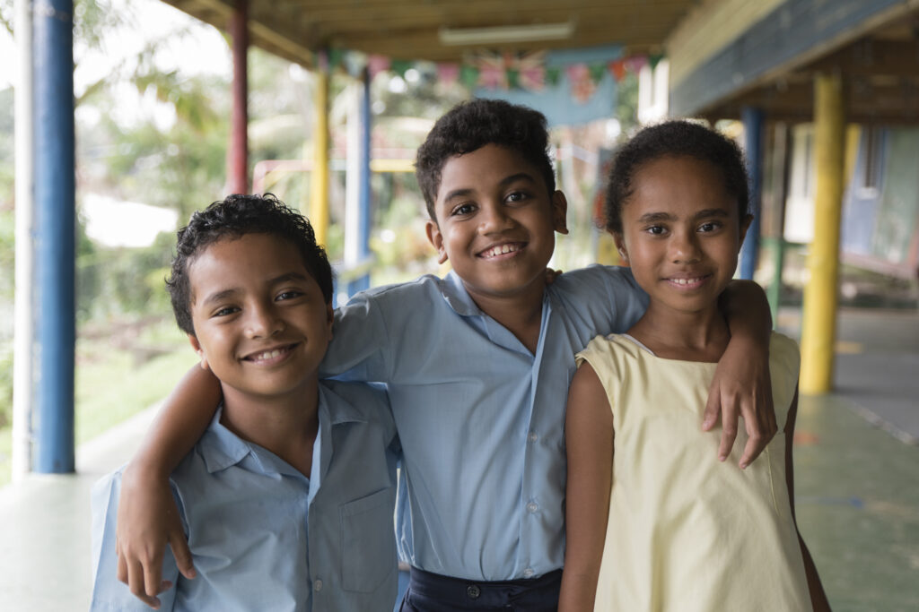 Three children from UNICEF Draw the Line TVC pose together at school