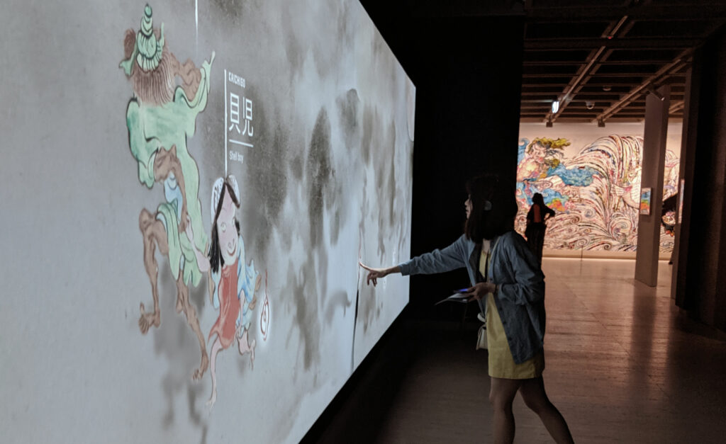 A woman engages with the interactive touch wall at the Art Gallery of NSW's Japan Supernatural exhibition