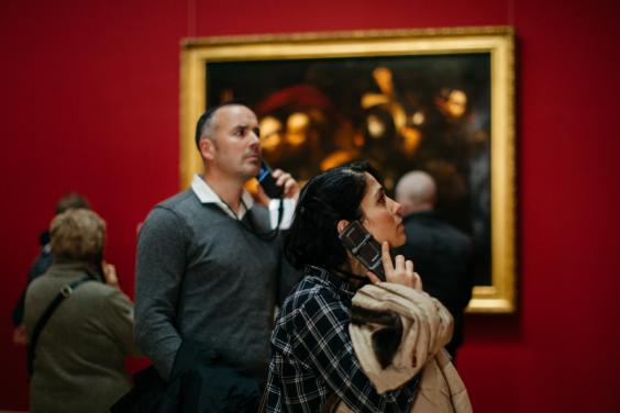Man and woman hold dedicated audio tour device to their ears in an art gallery