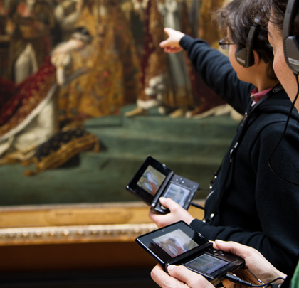 Two people hold Nintendo devices connected to headphones as they learn about an artwork from the Lourve