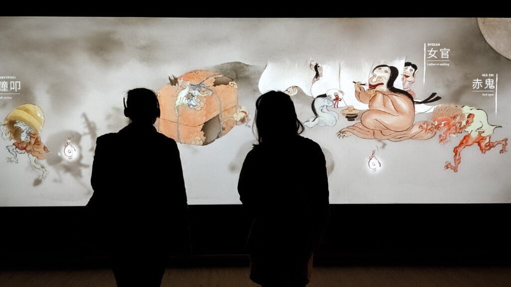 Silhouettes of two people stand in front of S1T2's interactive touch wall for the Art Gallery of NSW's Japan Supernatural exhibition