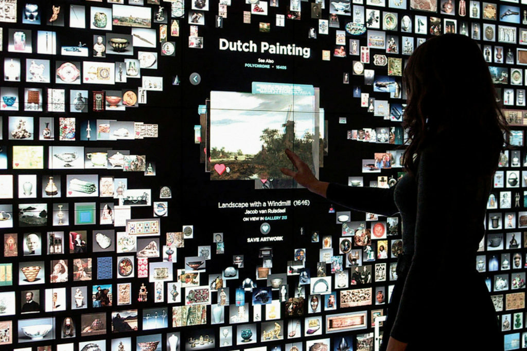 Woman interacts with information provided in the ARTLENS project through a large interactive touch screen