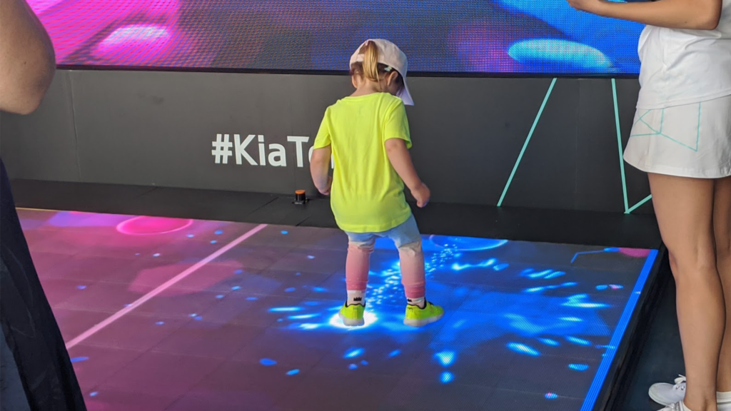 Small child interacts with LED floor of Kia Beat the Beat at the Australian Open.